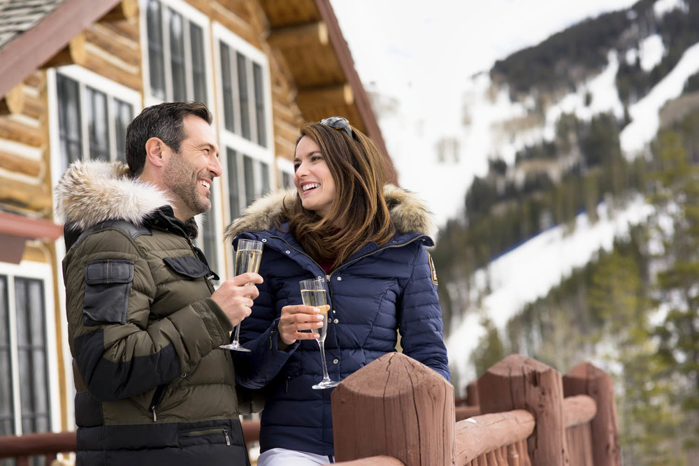 Wealthy couple drinks wine at Beano's Cabin in Beaver Creek Colorado. Lifestyle advertising photography.