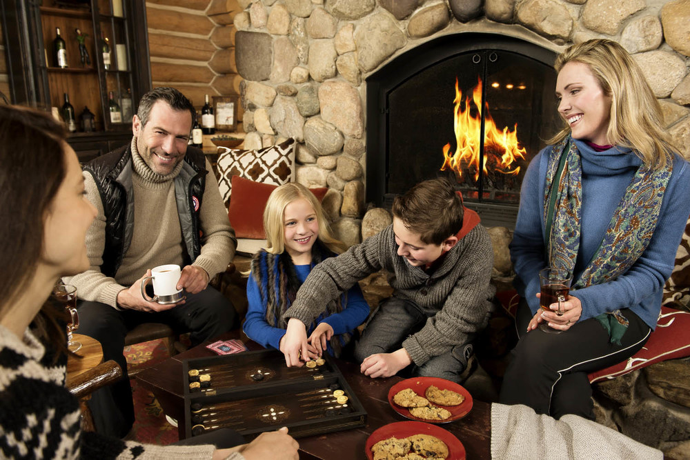 Family and group playing around fireplace at Beano's Cabin in Beaver Creek Colorado. Lifestyle advertising photography.