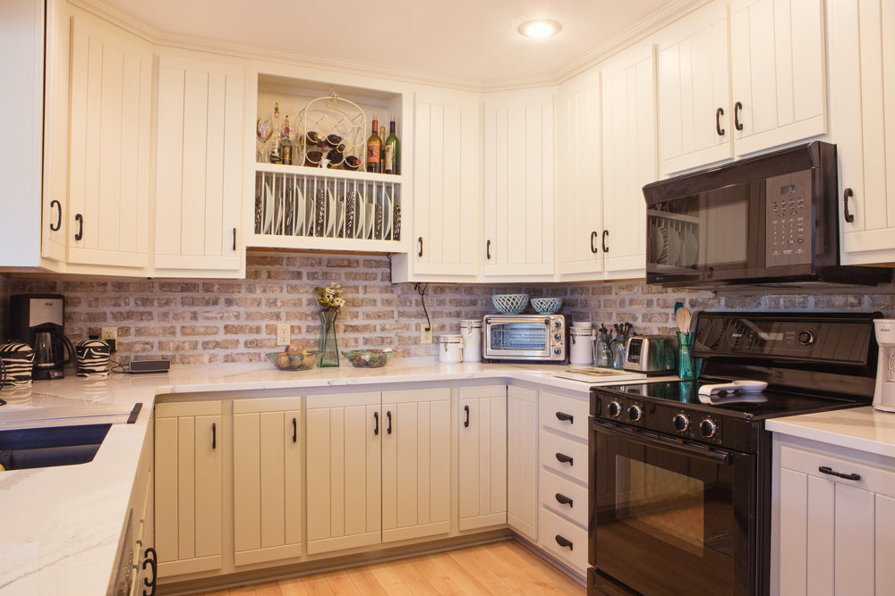 Painted Cabinets by Color Theory; new countertops and faux brick backsplash.