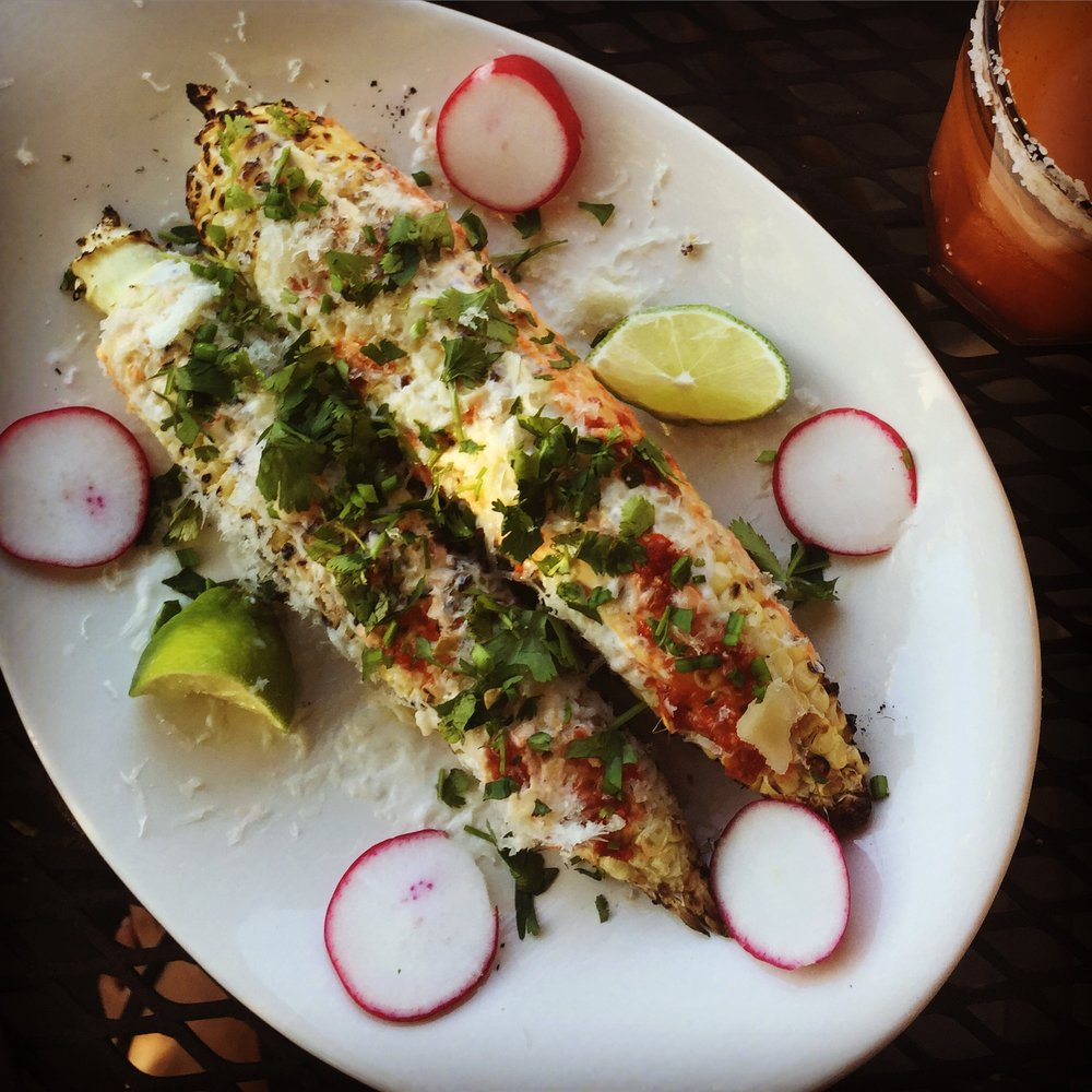 Mexican grilled corn elites with fresh cotilja cheese, spicy sauce, cilantro & lime