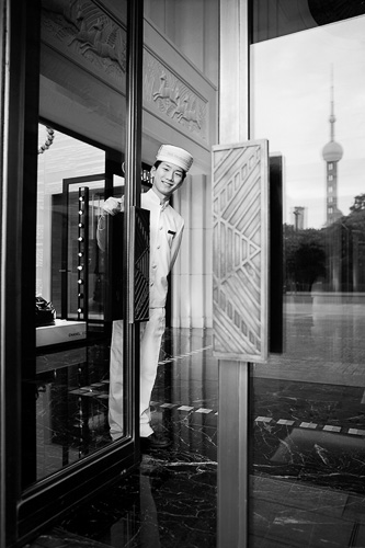 For the Pageboy greeting, it was very important to capture the reflection of the Pearl Tower in the hotel's front door. Daylight was used with one light to accentuate the warm welcoming smile of the pageboy.        在这张门童迎接贵宾的照片里,拍摄酒店前门里的东方明珠反光影像是非常重要的。除了要用一盏灯光照亮门童,来表现其温暖迎宾的微笑,其余大部分的影像都是利用自然光。此外,为了能够得到地板上更加清晰的反光影像,找到一个合适的曝光值十分重要。