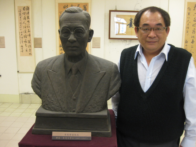 Joe Lin standing beside a bust of his grandfather Lin Mosei (林茂生)