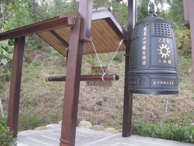 The Chinese characters on the left side of the bell, 氣蓋山河護台保國 from top to bottom can be loosely translated as: May the air above the mountains and the rivers protect Taiwan. Metaphorically, it means: Guarding Taiwan with immense righteousness. The characters on the center of the bell 自由鐘 translate as: Liberty Bell. The characters on the bottom of the bell 台灣即地大菩薩 can be loosely translated as: Bodhisattvas here in Taiwan. The metaphorical meaning would be: For those who have become great Bodhisattvas in saving Taiwan and protecting her people at this moment in this place.