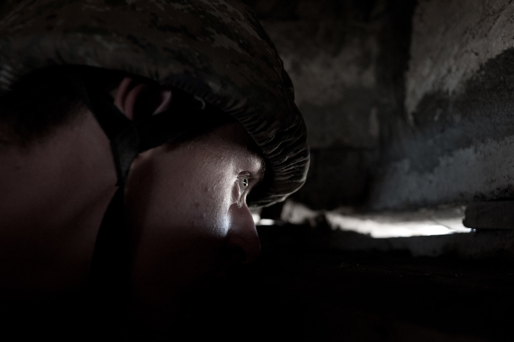 Arman, a young conscript from Voskevaz village, watches the Azerbaijani frontline located 30 meters from his lookout post on the Mataghis frontline, Nagorno-Karbakh.