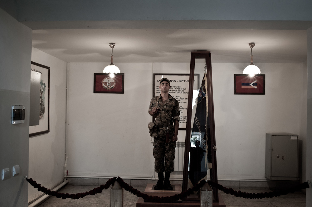"In two-hour shifts, a statuesque ""honorary soldier"" guards the flag of the Mataghis military unit at headquarters near Martakert, Nagorno-Karabakh."
