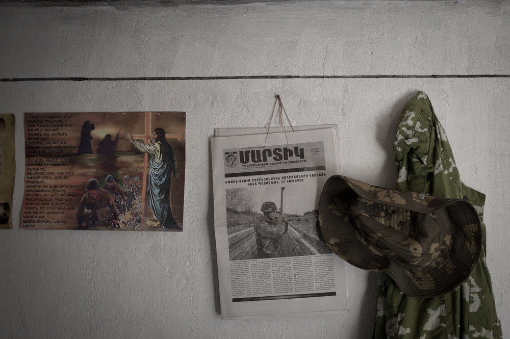 On the walls of a dugout on the Mataghis frontline hangs a religious poster discouraging violence among the military ranks, a soldier's hat and jacket, and a copy of the official military newspaper.