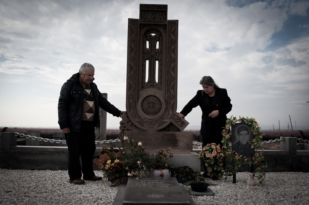 "Anahit and Aghasi at their son's grave. ""While serving, my son would describe how the battalion commander would grab soldiers by the collar and put his loaded gun to their heads to scare them. This is the same way my son was killed."""