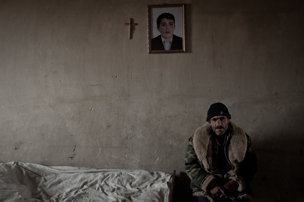Meguerdich Meguerdichian sits next to the bed where his son Jora died in 2012. While serving at the Yeghnikner military base, Jora was severely beaten and fell into a coma. He later died at home in Lousakn village.
