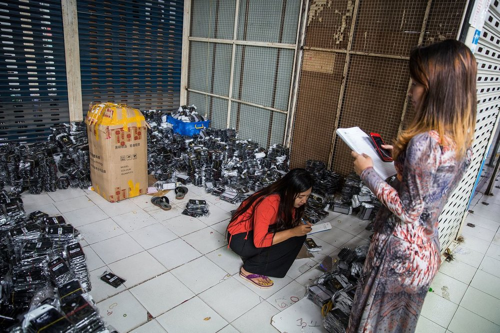 An employee make notes as she takes inventory of mobile phone accessory at a store in Yangon.