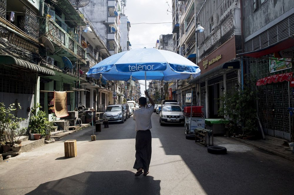 A man carries a Telenor parasol in Yangon.