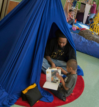 Jamir and his dad reading in the light tent at Red Hook Space.  (photograph by Kate Milford)