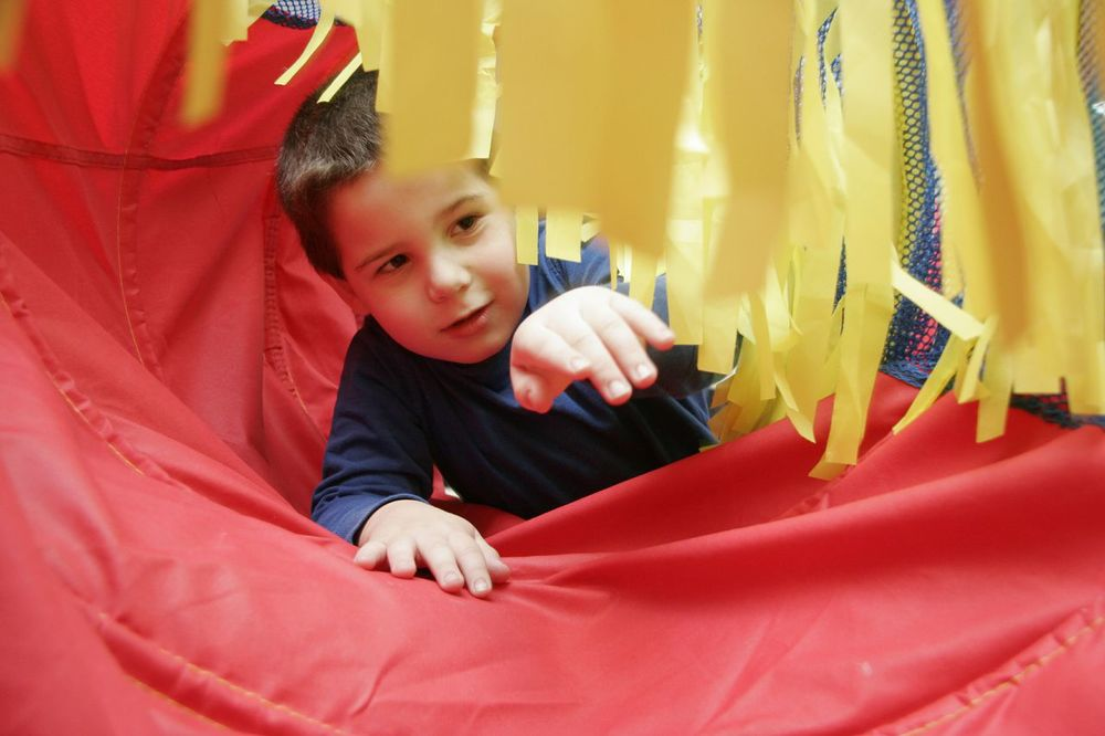 Quentin, who is minimally verbal with  PDD-NOS (or  Autism,     however you want to define it) , is a  sensory-seeker . To   people who have never   met him, I often describe Quentin as Curious George - a   good little monkey, but   sometimes a bit too curious. At Extreme Kids, his curiosit  y is allowed to become   unleashed. He loves the  tunnel  because it provides him wi  th a comforting   enclosed space to crawl through, but then there are th  ese surprise fabric pieces   to explore! Sometimes his twin sister, Fiona, will craw  l through behind him,   sharing his experience. We are so happy to have a safe  sen    sory-filled  space   where we can relax as he explores!""