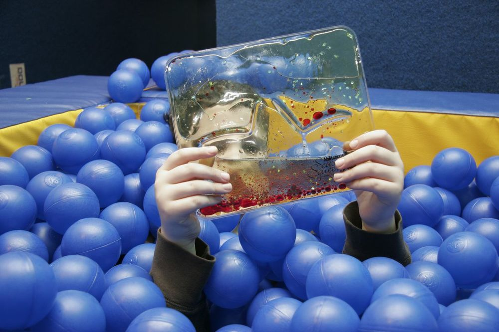 """My son Louis has  significant sensory needs , and there are  times when the only thing that makes him happy is being a  t the sensory gym. He   tried out everything at Extreme Kids, of course, but fr  om day one he spent most   of his time in the  ballpit . It gives him th  e sort of  full-body input  that he   needs, and he would spend hours just lying there if he   could. And, of course, he   loves to throw the  balls  out and make a mess."""