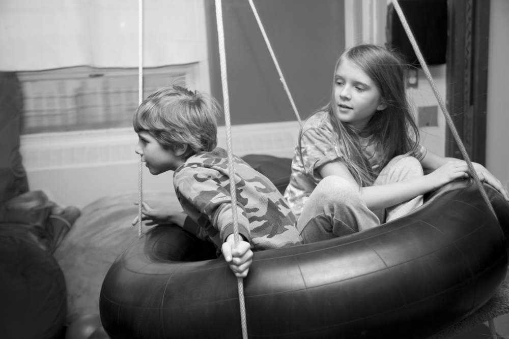 Shane and Rosey, siblings, in the tire swing at AMP.  (Photograph by Kate Milford)