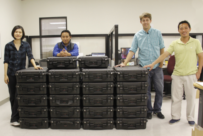 Members of the Crystal Instruments production team pose with a stack of CoCo-80 handheld vibration monitoring devices ready for shipment in June 2015
