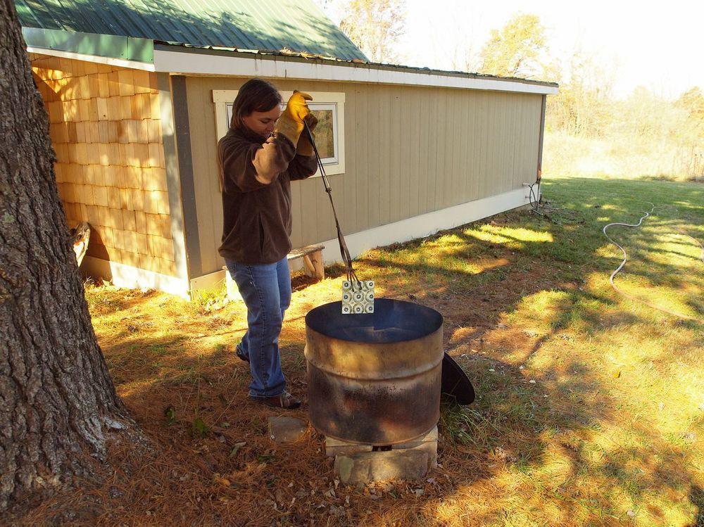 Clare adding a hot tile to raku pit.