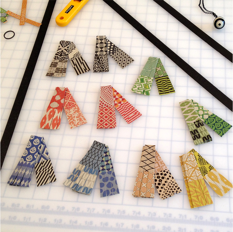 Pendants, ready for assembly. Each has a printed linen tassel with custom illustrated patterns.