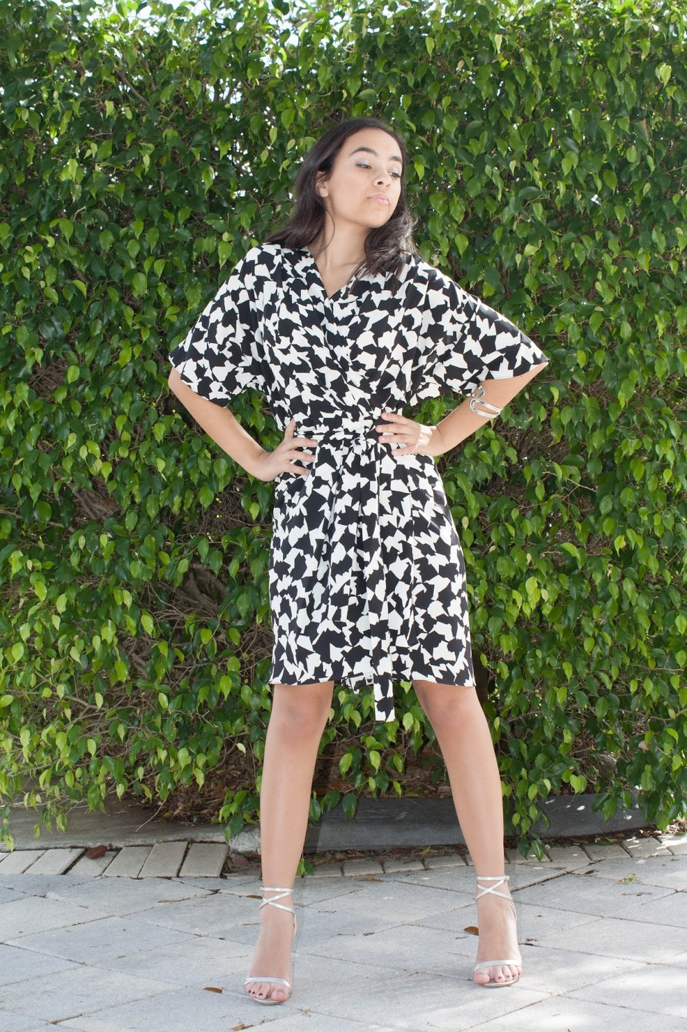 black and white spring dress in front of green bush.jpg