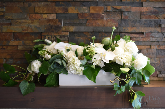 White wedding arrangement with roses, ranunculus, lisianthus, ornitho, orchid, succulents and ivy by Celsia Floral.