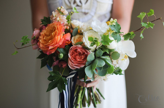 Colourful bridal bouquet of garden roses, pin cushion, lisianthus, orchid, craspedia, succulents and ivy by Celsia Floral.