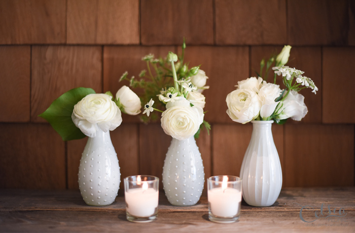 White floral votives of ranunculus and lisianthus.