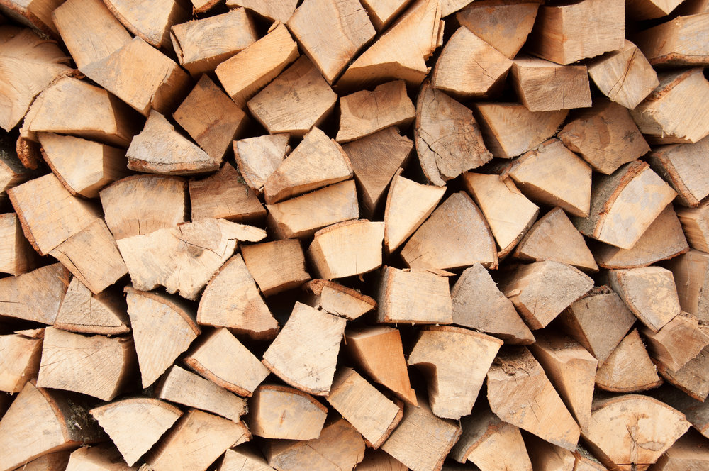Background of dry chopped firewood logs in a pile.jpg
