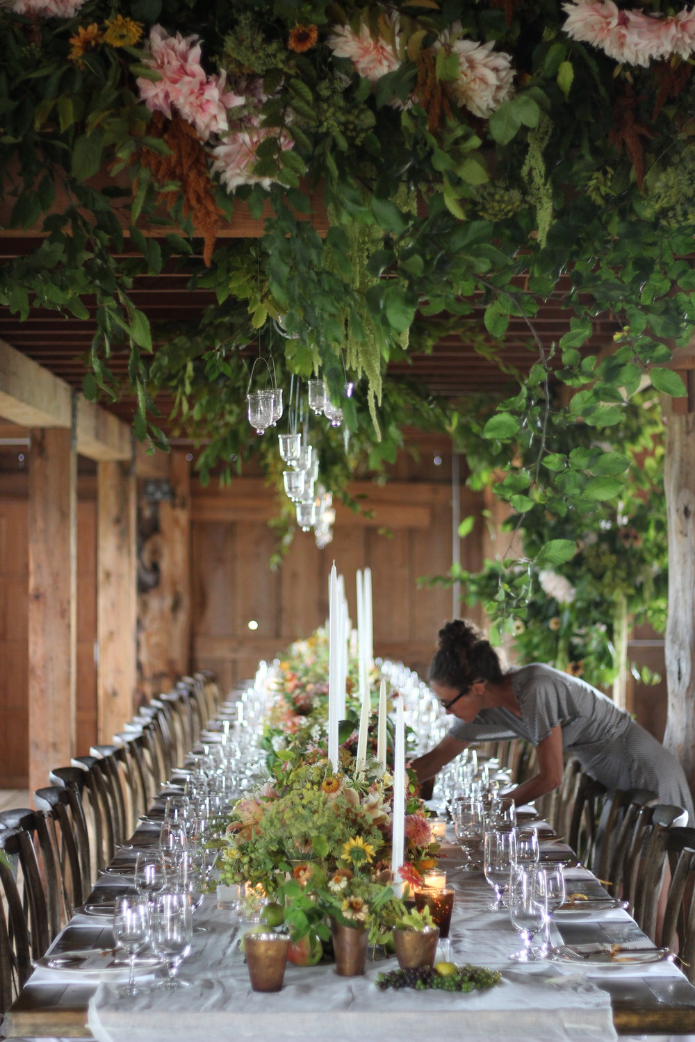 Gretchen O'Neil, fellow team member, lighting candles.  Table design by Becca Blue and floral installation by Sue McLeary.