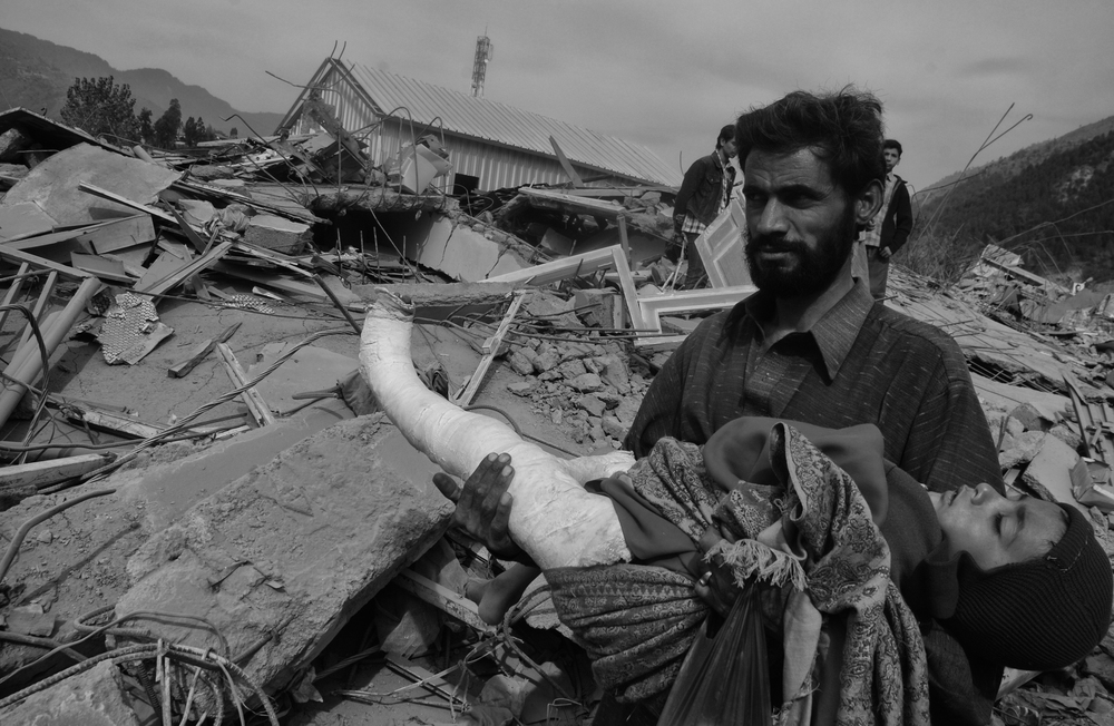 A father carries his injured daughter through the destroyed town of Balakot, NWFP, Pakistan, October 18, 2005. (Photo/Mark Pearson) The massive October earthquake in Kashmir affected one of the highest and most remote places on earth. Difficult terrain slowed the relief effort and the largest scale humanitarian air operations since the Berlin blockade began.