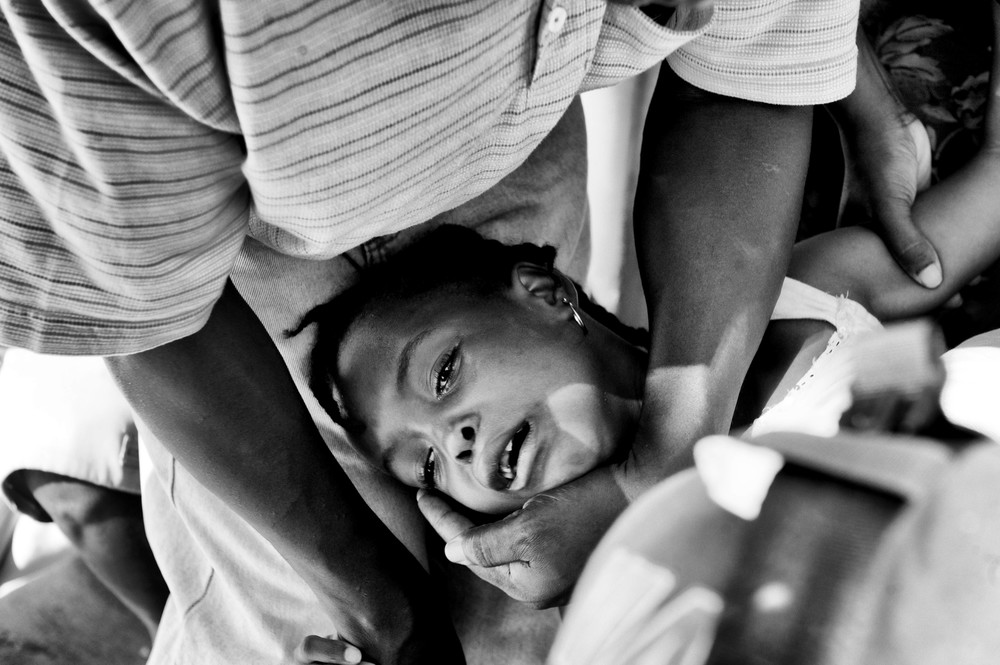 A young girl who was seriously injured from the earthquake receiving  surgery outside the General Hospital, Port-au-Prince, Haiti, January 15, 2010. More than 230,000 are believed to have died in the earthquake, and more than a million were made homeless. (Photo / Mark Pearson)
