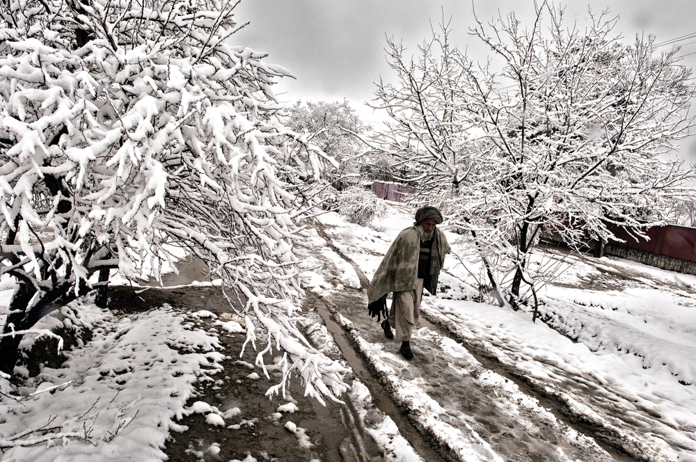 An elderly Afghan man walks through snow in Maymana, Faryab Province, Afghanistan, February 21, 2008. (Photo/Mark Pearson)