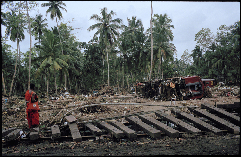 "A Buddhist monk scans the wreckage of a train called "" the queen of the sea "" hit and derailed by a series of Tsunamis that hit Sri Lankas coastal regions on the 26th December, 2004. (Photo/Mark Pearson)"