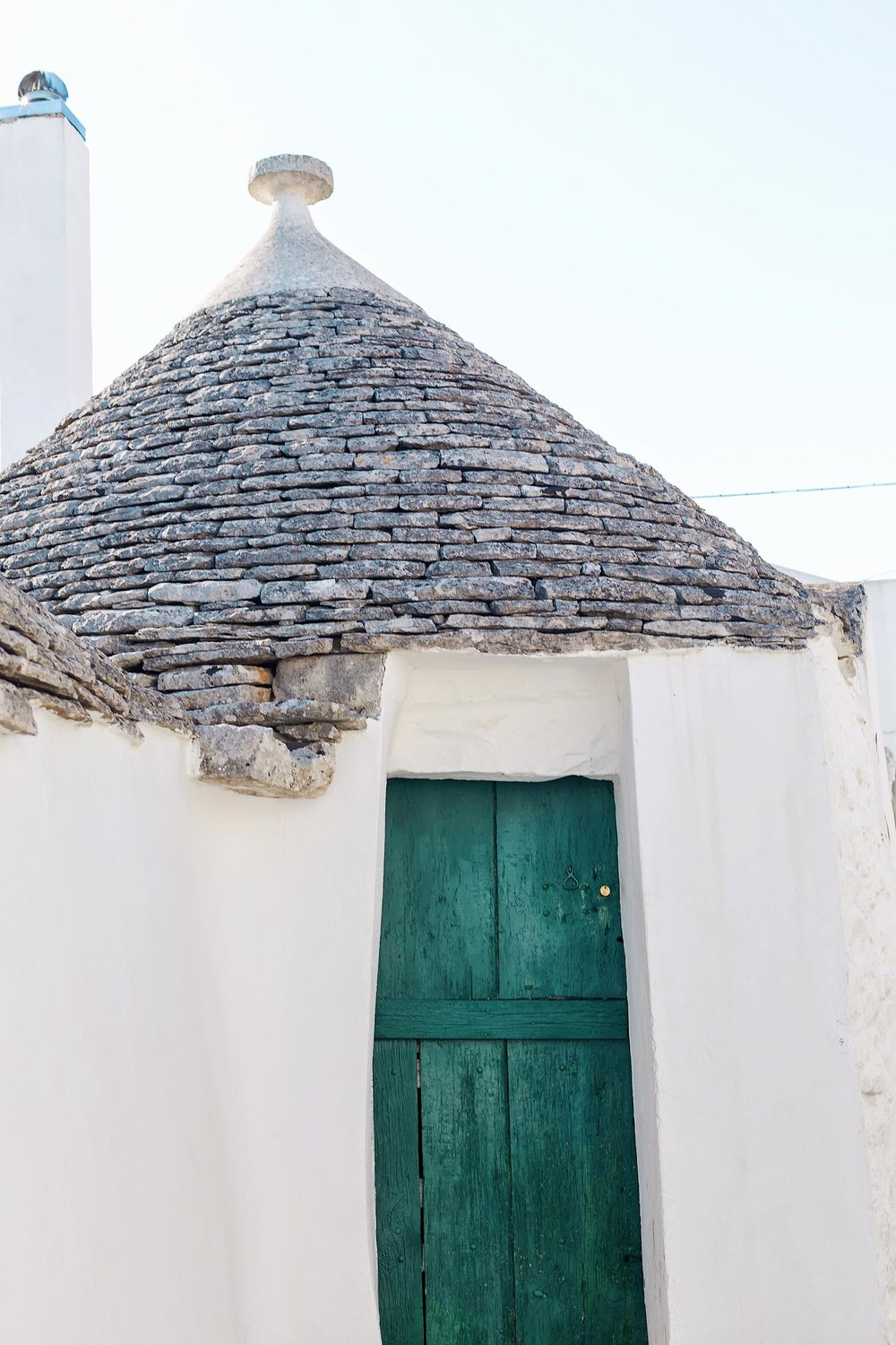 A teal door on a trullo building in Puglia