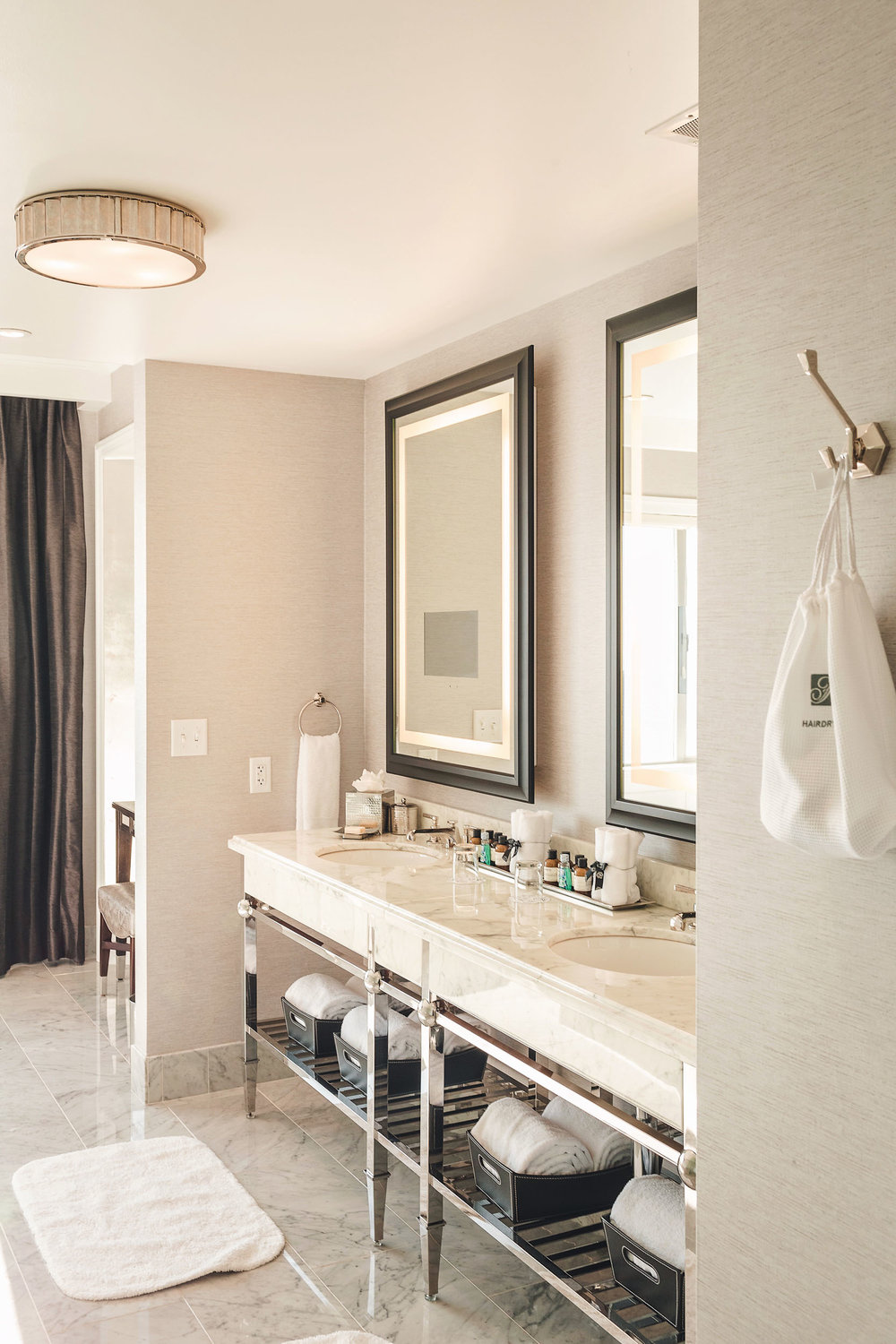The spa bathroom in the Presidential Suite at the Fairmont San Francisco is beyond glamorous and includes a double vanity, marble shower and an infinity bathtub with city views