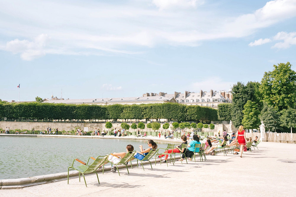 Summer in Paris - the Seine is lined with people dangling their feet over the edge, the Eiffel Tower lawn with picnic-goers, and every cafe, restaurant, and bar with outdoor diners.