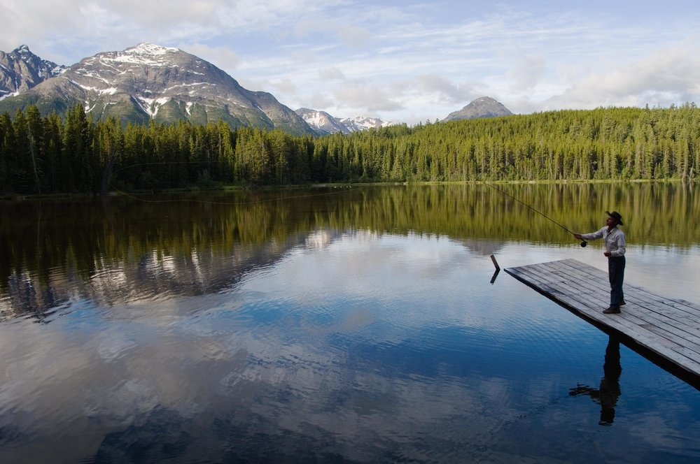 Fishing from a dock with views of the mountains at Cheshi Lake. Credit: Destination BC/Albert Normandin