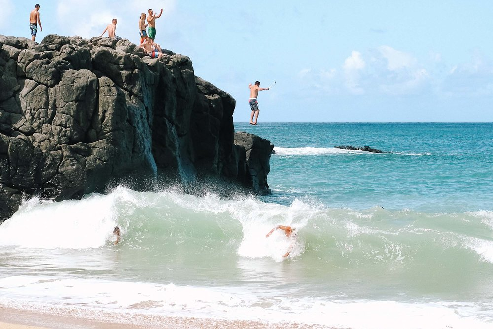 Jumping off a rock at Waimea Bay