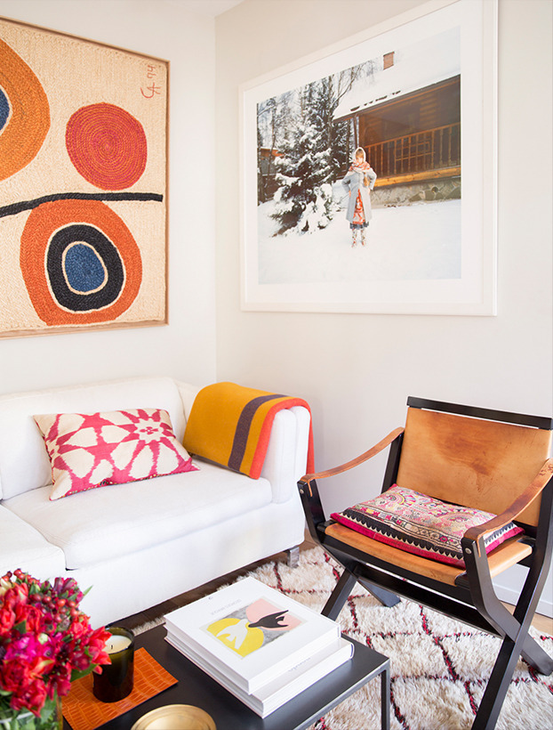 In the living room, a framed Alexander Calder tapestry   and an Anna Skladmann photograph highlight the burnt   oranges and reds of the surrounding furnishings.