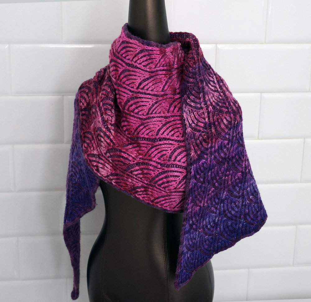 - sashiko brioche wrapThis fluffy, textured wrap features a stitch pattern inspired by traditional Japanese sashiko embroidery. If you've done basic brioche before or you're new to brioche but feeling adventurous, this project is for you!The finished wrap can be worn in a number of ways. Turn back one edge to form a faux collar featuring the color from the opposite side, wear it like a scarf, or wrap it around and add your favorite shawl pin. The tapered corners give it a polished, elegant look no matter how you wear it.