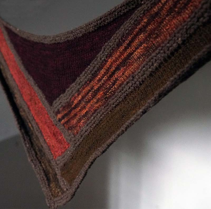 - log cabin scarfWith long, sweeping lines that intersect in a bold central motif, this unusual scarf's best feature is the opportunity it provides to play with color and texture - it looks brilliant in solid, semi-solid, textured, and variegated yarns.Requires 50 y / 46 m x 5 colors of Aran-weight yarn, plus 100 y / 92 m for borders and edging.Pattern available here.