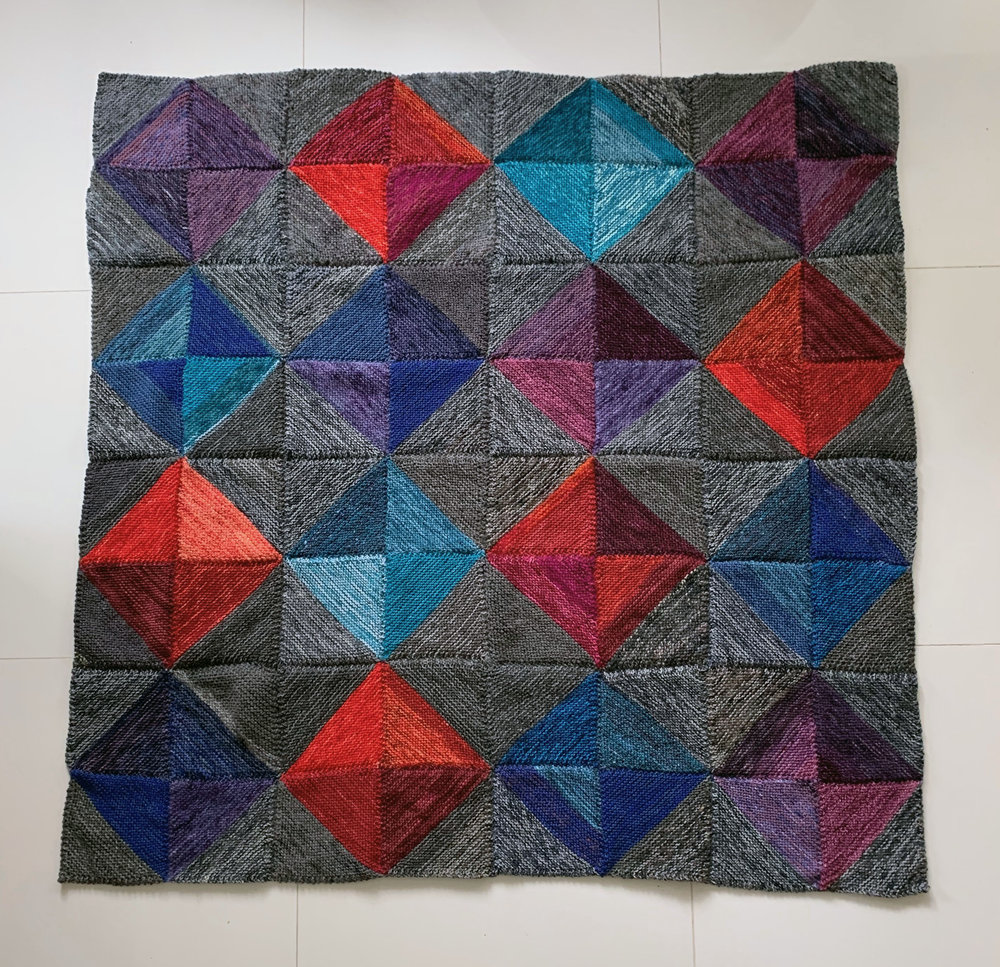 - knitter's quilt: dancing diamondsInspired by patchwork quilting, this cozy diamond-motif blanket makes your scrap yarn shine.The knitting directions are easy to memorize, almost any yarn weight can be included, and the yarn requirements for each square are so scant that this project will fit in even a sandwich-size bag. There is simply no better on-the-go knitting. If you knit a square every time you find yourself with a few spare minutes, you'll have a blanket in no time.Pattern available here.