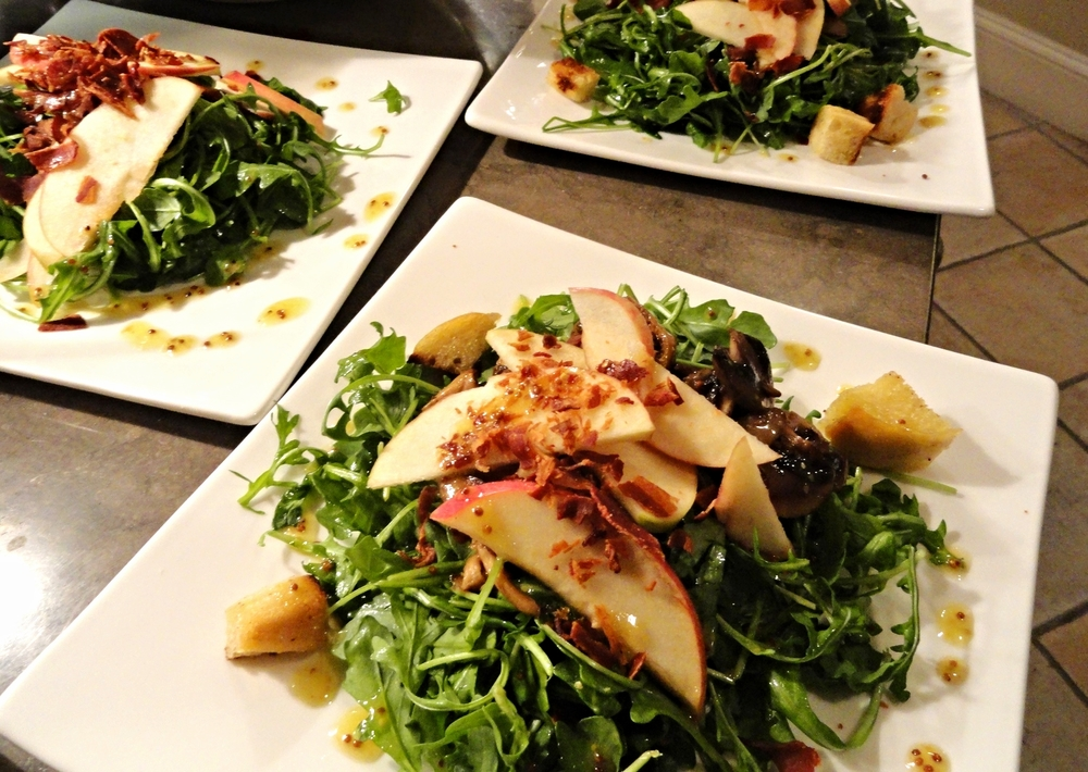 Arugula salad with apples, pecans, crumbled bacon, croutons, and whole grain mustard vinaigrette