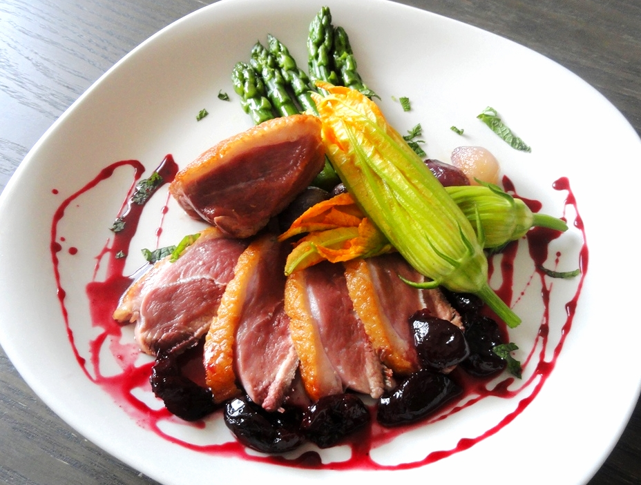 Pan-seared Long Island duck breast with asparagus, zucchini flowers, and a cherry-port reduction