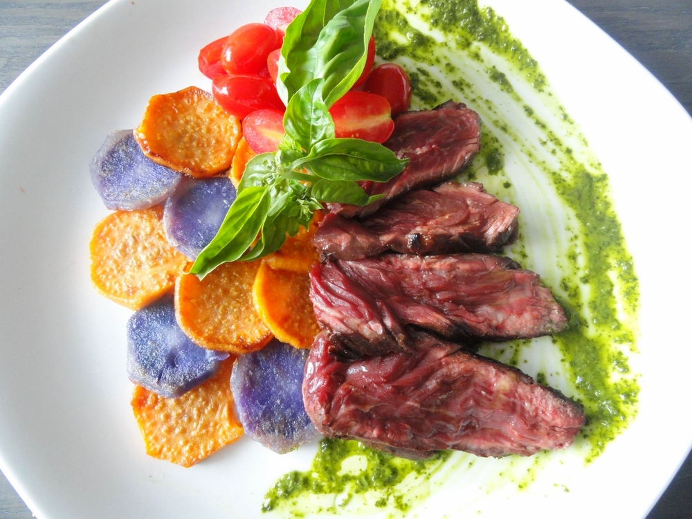 Seared beef controfiletto on chimichurri sauce with sweet and purple potato medallions