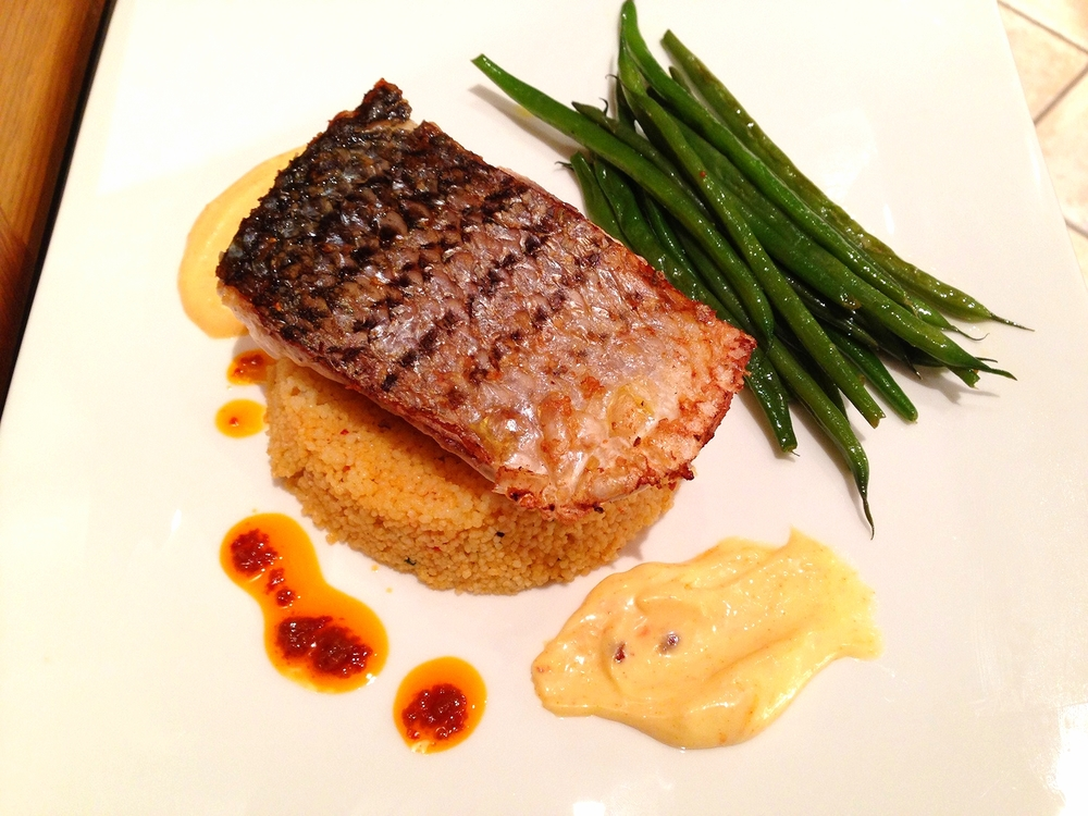 Striped bass on harissa couscous with haricots verts and saffron aioli