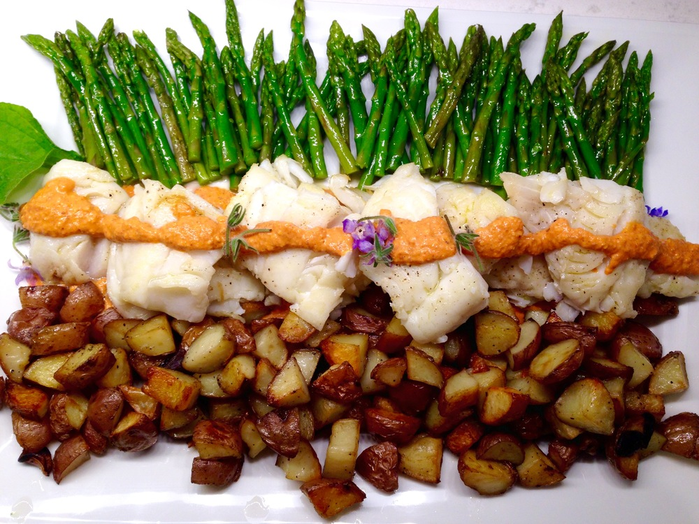 Cod fillets with romesco sauce, garlic-rosemary roasted potatoes, asparagus tips
