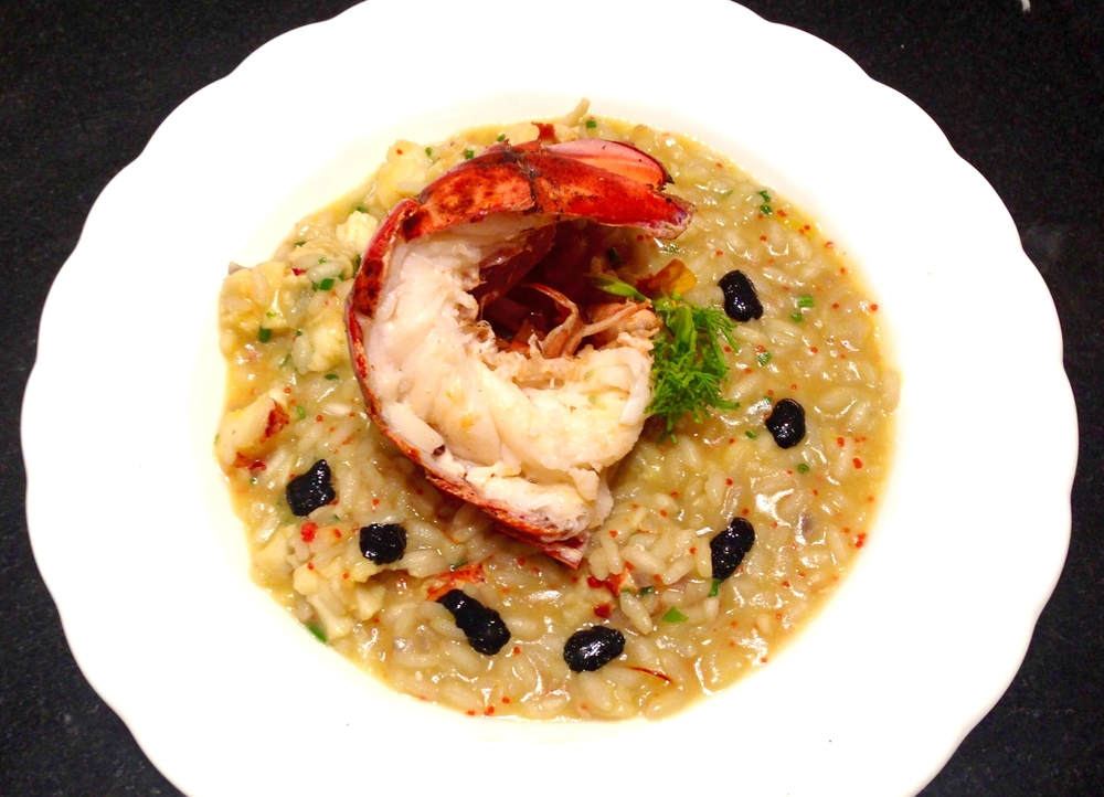 Lobster risotto with roasted lobster tail, lobster roe, chives, and squid ink sauce