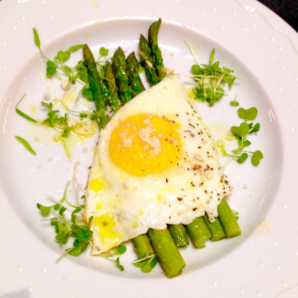 Olive oil-cooked egg on asparagus spears with microgreens, parmigiano, and truffle butter