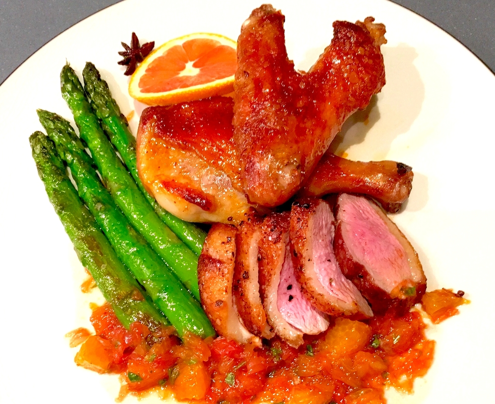 Roasted duck breast and leg with spiced citrus sauce and seared asparagus
