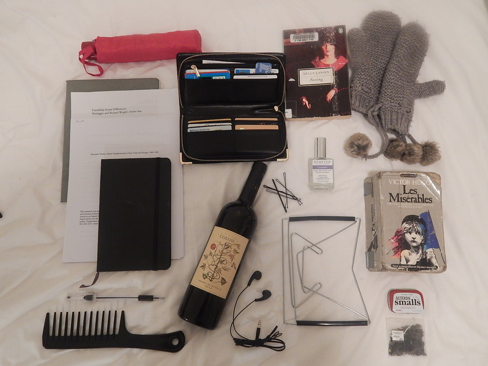 "1. One red H&M umbrella / 2. One black Aldo wallet with gold zipper / 3. Passing by Nella Larsen / 4. One pair of grey H&M mittens / 5. Les Miserables by Victor Hugo / 6. 1 fl. oz / 30 ml of Lavender scent by Demeter Fragrance Library / 7. Travel size Altoids Smalls / 8. Tazo Earl Grey tea bag / 9. Book Holder / 10. Pair of Sony earbuds / 11. 2012 Nero D'avola bottled by Cantine Colosi / 12. Conair extra long bobby pins / 13. Wide-tooth (and afro-friendly) plastic comb / 14. Black Pentel RSVP ball point pen (the ONLY pen I write with) / 15. Black blank-paged hardcover Moleskine (the ONLY thing I journal in) / 16. Essay on top: ""Emergent Ghettos: Black Neighborhoods in New York and Chicago, 1880-1940"" by John R. Logan of the Department of Sociology at Brown University, Weiwei Zhang, and Miao David Chunyu / 17. Essay Underneath: """"Friendship Across Differences: Heidegger and Richard Wright's Native Son"" by Sharin N. Elkholy / 18. Grey blank-paged paperback Moleskine"