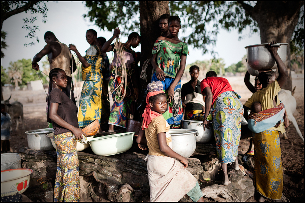 A girl, surrounded by other girls and women, looks into the camera at Mokolo Kambaya, Tandjilé, Chad on 27 April 2015. The 15 meter deep water well is the only water source within a radius of 20 km and so, some women have sometimes to walk for hours to get fresh water.